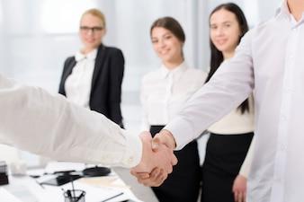 Два деловых партнера пожимают друг другу руки в офисе