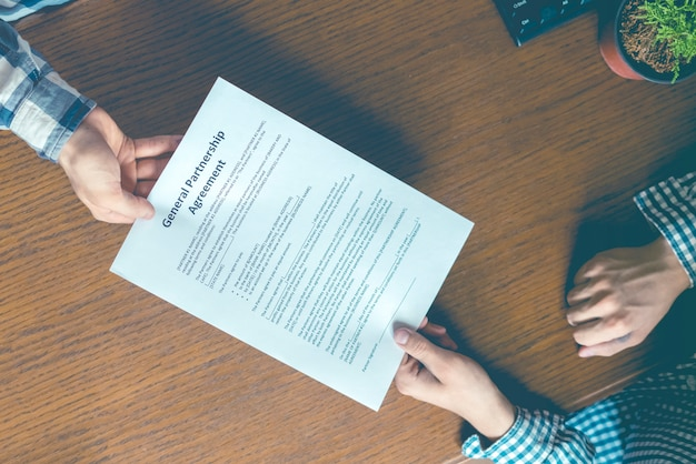 Two business partners sign partnership agreement in the office table , an overhead toned image