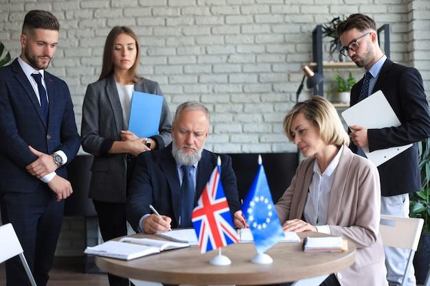 ドキュメントに署名する2つのビジネスパートナー。欧州連合イギリス。