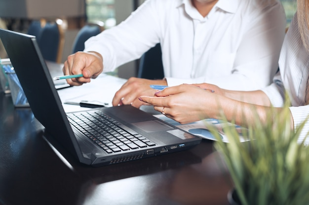 Two business partners sitting at a table together and working.