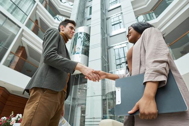 Two business partners standing outdoors with building in the background and shaking hands