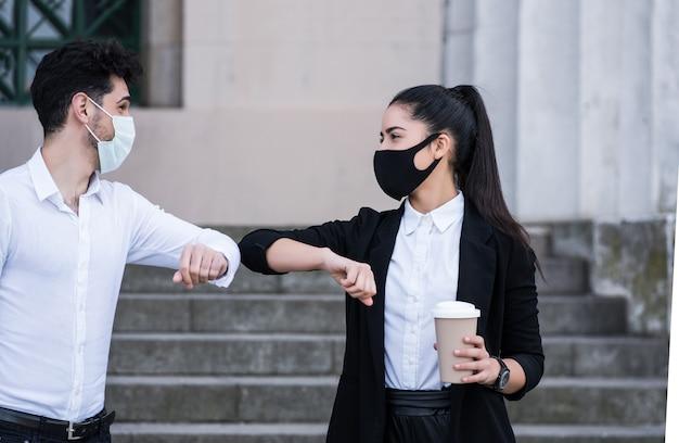 야외에서 서로 인사하기 위해 팔꿈치를 부딪 치는 두 비즈니스 사람. 비즈니스 개념. 새로운 정상적인 생활 방식.