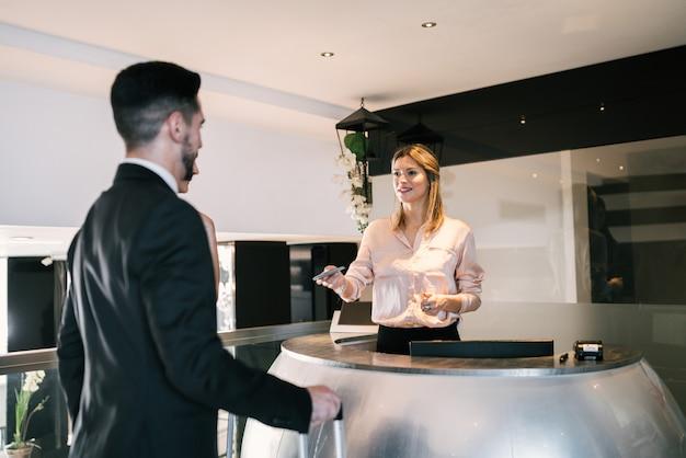 두 비즈니스 사람이 호텔 리셉션에서 체크인합니다.