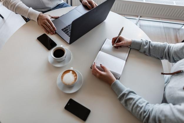 두 비즈니스 사람들이 카페의 테이블에 앉아있는 동안 작업 순간을 논의하고 커피를 마시는