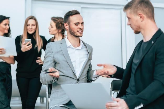 Два деловых человека обсуждают что-то на встрече в офисе