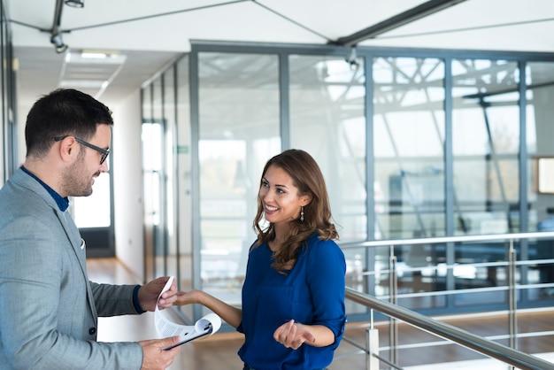 회사의 복도에서 대화를 나누는 두 비즈니스 사람.