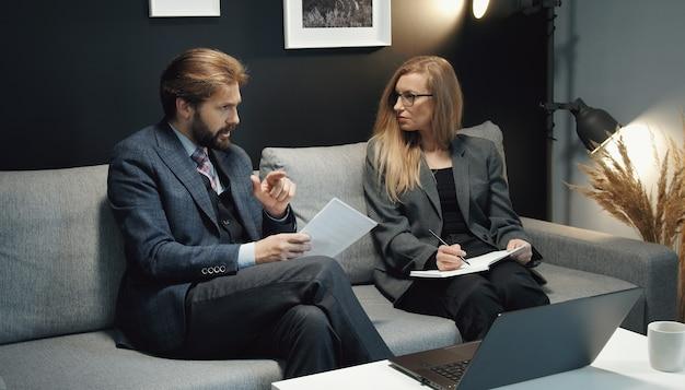 Два деловых человека, мужчина и женщина, обсуждают идеи, сидя вместе на диване перед ноутбуком