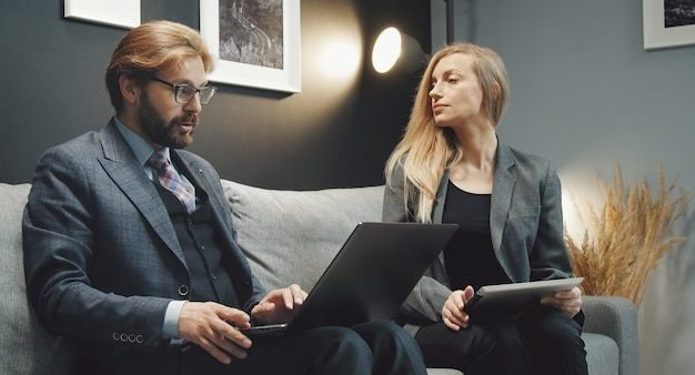 Два деловых человека, мужчина и женщина, обсуждают идеи, сидя вместе на диване с цифровыми гаджетами