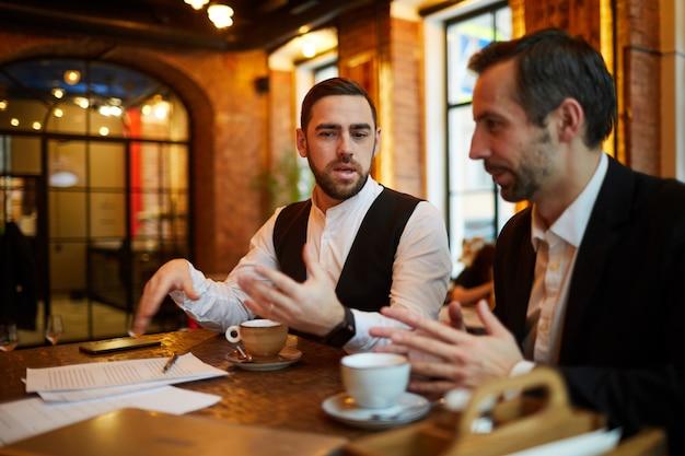 レストランで会う2つのビジネス人々