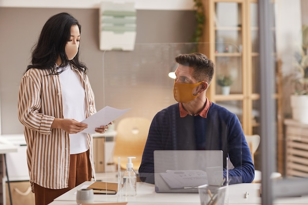 Two business people wearing face masks while discussing project in office, copy space