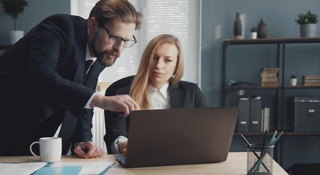 Два деловых человека, работающих вместе, обсуждают важные вопросы с помощью портативного компьютера в офисе