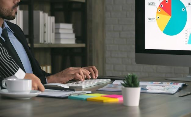 オフィスで一緒に働く2人のビジネスマン。ビジネスウーマンが彼の隣に立っている間、オフィスの机に座って、デスクトップコンピュータを使用しています。