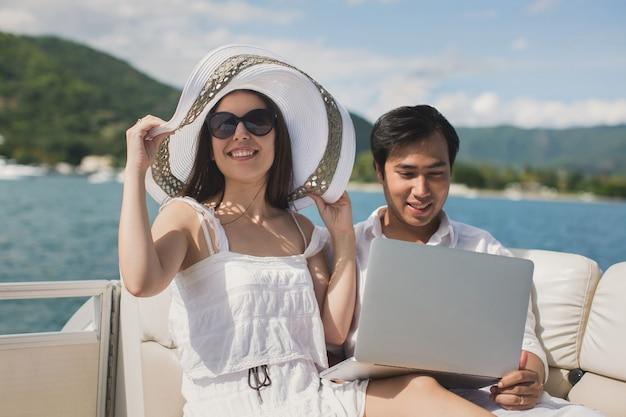 항해 보트에 노트북을 사용하는 두 비즈니스 사람. 항해 여행.