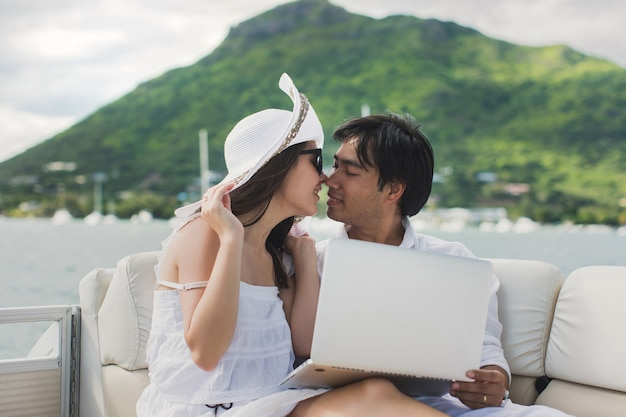 Two business people working with laptop on a sailing boat. sailing trip.