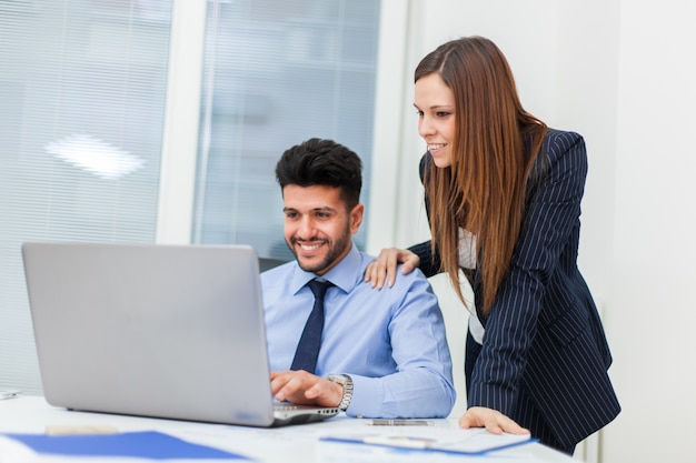 Two business people working with a laptop