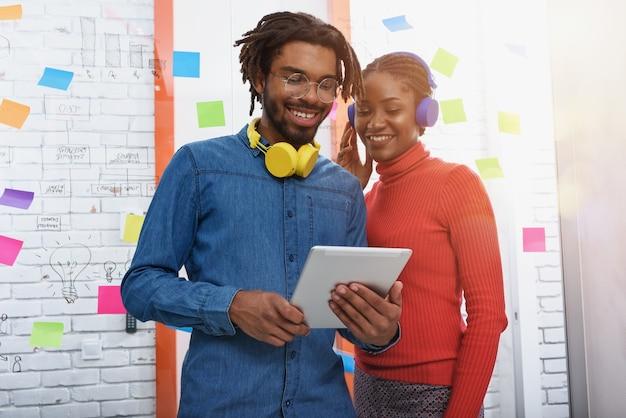 두 명의 비즈니스 사람이 태블릿으로 사무실에서 함께 작업합니다.