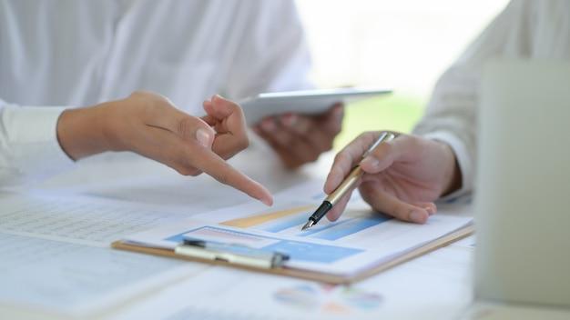 2つのビジネスチームが、オフィスで一緒に働いているプロジェクトのグラフについて議論し、分析します。