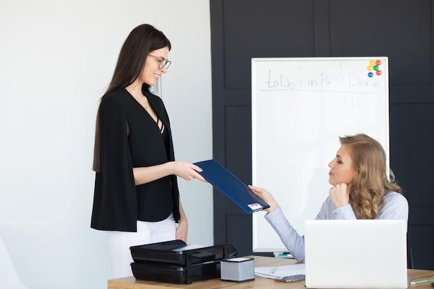 2つのビジネスの女性投資コンサルタント会社の年次財務報告書バランスシートステートメントドキュメントグラフの操作を分析します。経済、市場、オフィス、お金および税の概念図。