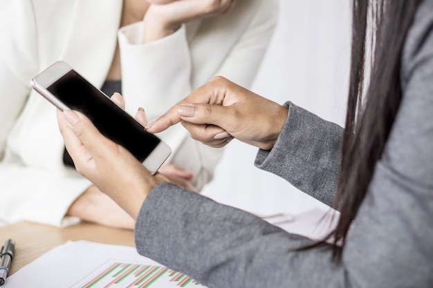 Two business woman looking at mobile phone working together