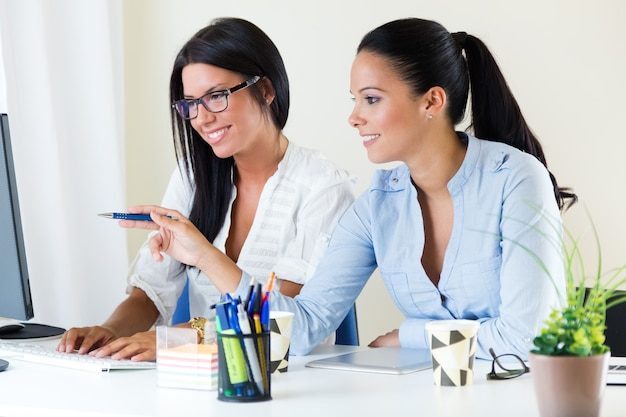 Two business woman working in office with computer.