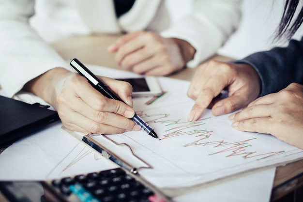 Two business woman working together analyzing financial graph