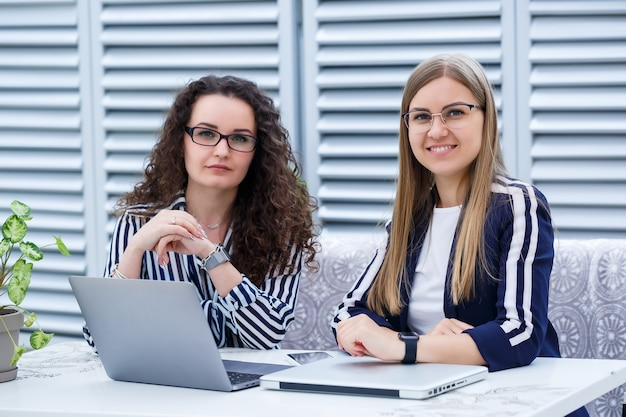 Two business women are sitting in a bright cafe with a laptop and business papers and talking with serious people. office workers are sitting on coffee breaks and working. business meeting in a cafe