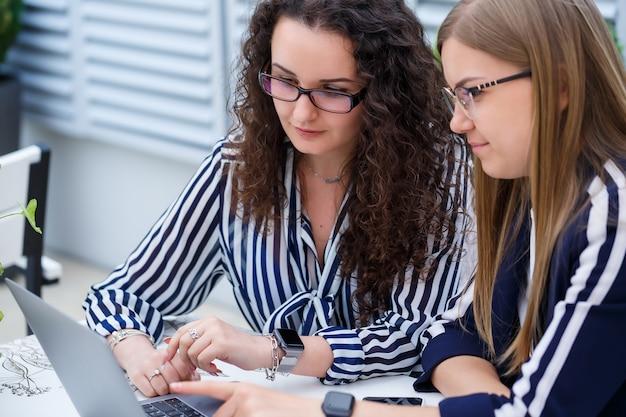 두 명의 비즈니스 여성이 노트북과 비즈니스 서류가 있는 밝은 카페에 앉아 진지한 사람들과 이야기하고 있습니다. 직장인들은 휴식시간에 앉아서 일하고 있습니다. 카페에서 비즈니스 미팅