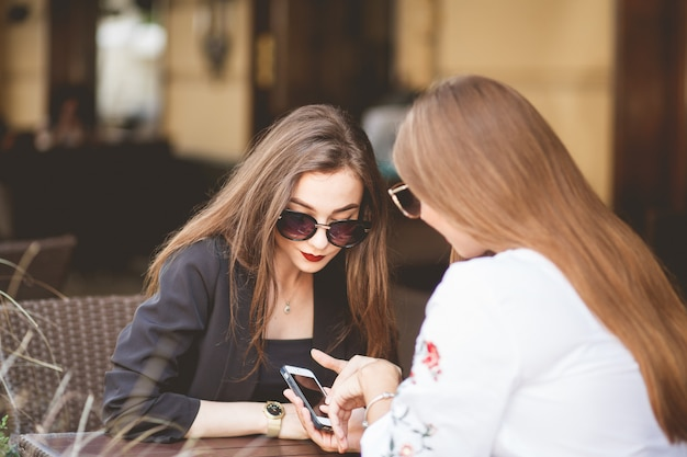 カフェで2人のビジネス女性とスマートフォンで見ています。 1対1-レストランのテラスで電話で2人の女性に会う