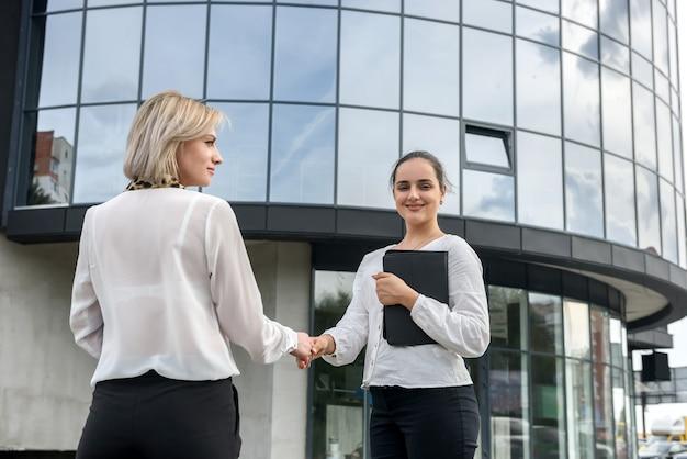 オフィスビルの前で握手を交わすスーツ姿のビジネスウーマン2人