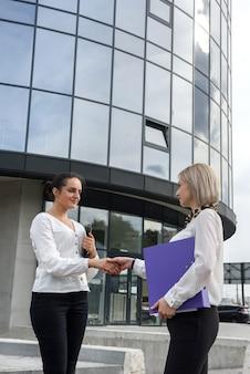 Две бизнес-леди в костюмах пожимают друг другу руки перед офисным зданием