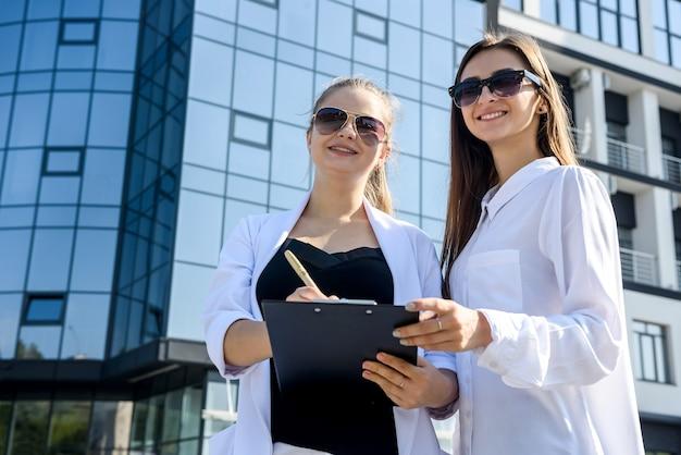 大きなオフィス センターを建設する前に、屋外で契約書に署名する 2 人のビジネス女性