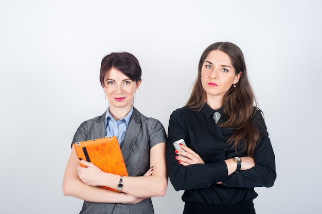 Two business women standing on a light with your arms crossed