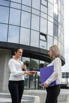 Two business women in suits handshaking before office building