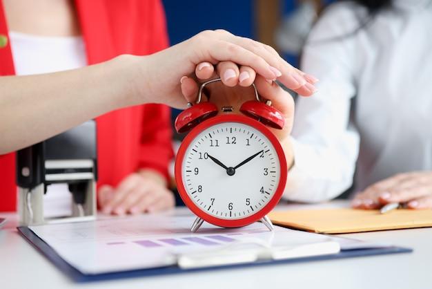Две деловые женщины выключают будильник на рабочем месте крупным планом
