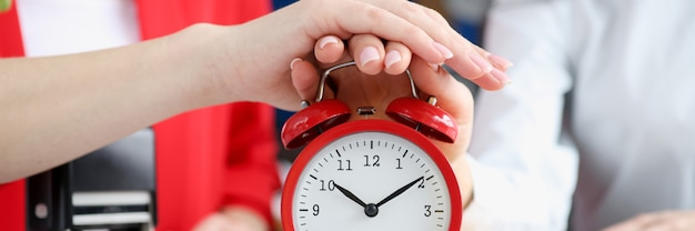 Two business women turning off alarm clock at workplace closeup