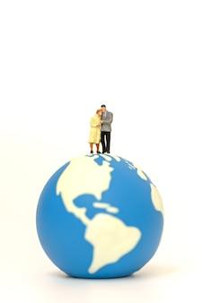 두 명의 사업가 및 사업가 미니어처 그림 사람들이 미니 월드 볼을 걷고 서 있습니다.