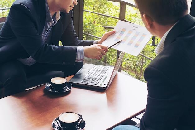 コーヒーショップで彼らのチャートを議論する2つのビジネスマン