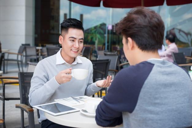 街でカジュアルな会議や話し合いをする 2 人のビジネスマン。