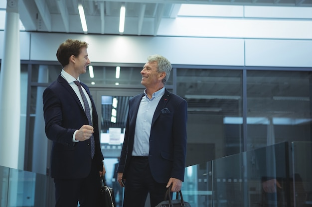 Two businessman interacting with each other in corridor