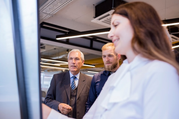 Two businessman looking at smiling woman giving presentation on flip chart