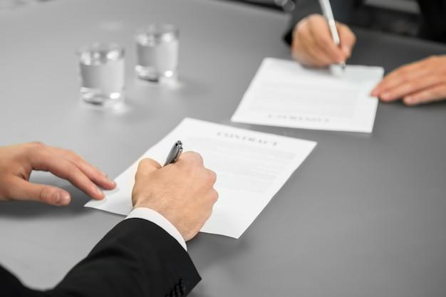 두 사업가가 거래를 합니다. 기업 계약입니다. 보장을 제공합니다. 모든 것이 공식적입니다.