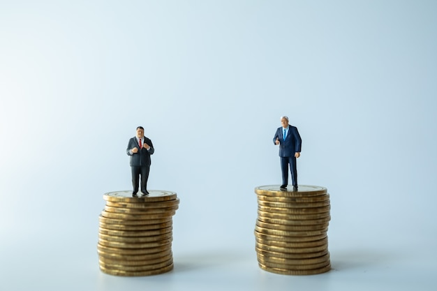 Two businessman miniature figure people figure standing on stack of coins.