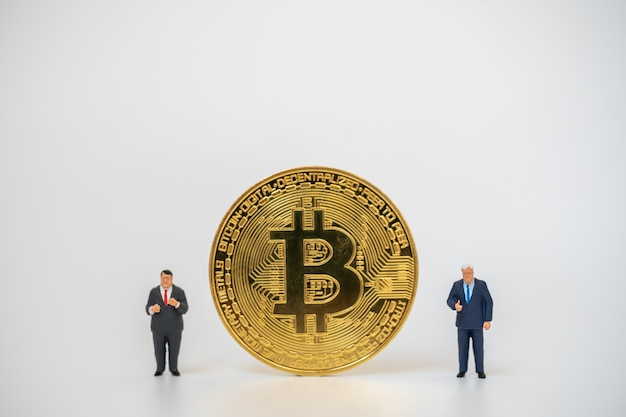 Two businessman miniature figure people standing with gold bitcoin coins on white background