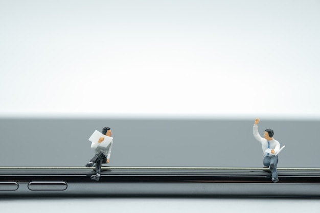 Two businessman miniature figures sitting and reading a book and talking on smart phone.