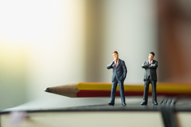 Two businessman miniature figures standing on black notebook with pencil.