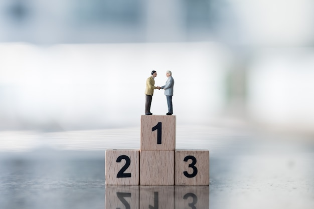 Two businessman miniature figures standing and handshake on wooden number one block.
