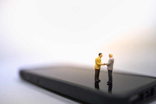 Two businessman miniature people figures standing, talking and hand shake on smart mobile phone.