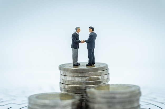 Two businessman miniature standing on stack.