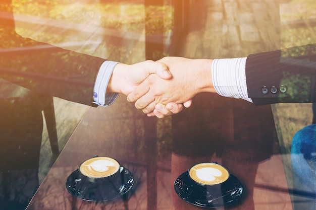 Two businessman shake hand in coffee shop