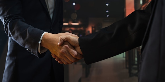 Two businessman shake hand with partner